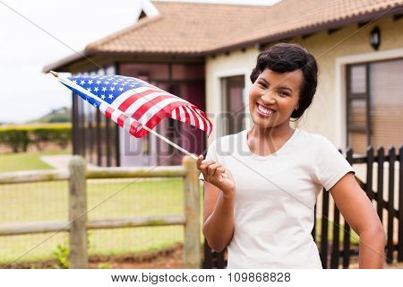 portrait of pretty black woman with USA flag in front of her house