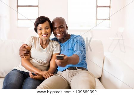beautiful african couple watching movie together at home