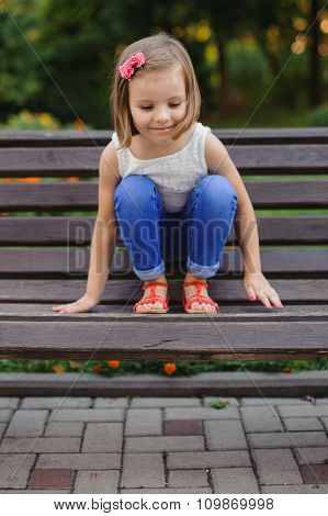 Little Cute Girl Sits On Bench