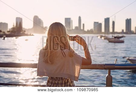Blonde girl in glasses taking picture of city bay with mobile phone on sunset. Focus on smartphone
