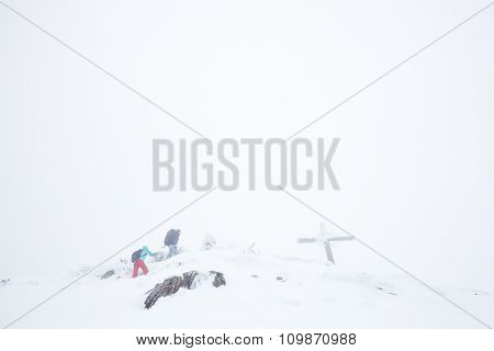 Male and female mountain climbers with backpacks and trekking poles successful finishing their extreme winter hiking trip to top of mountain with cross during blizzard in Austrian Alps