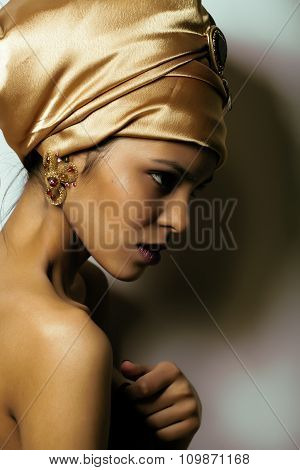 beauty african woman in shawl on head, very elegant look with gold jewelry close up mulatto