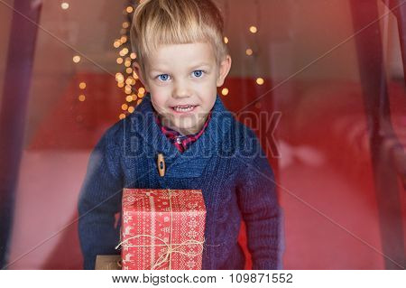 Smiling funny child holding Christmas gift in hand. Christmas concept. Birthday