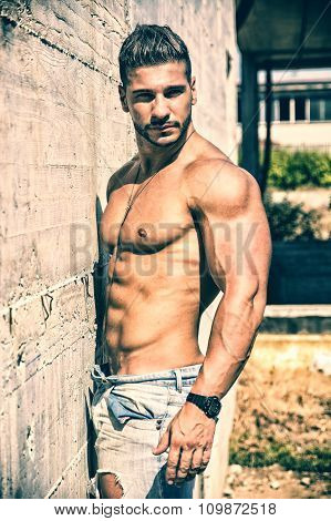Shirtless bodybuilder against concrete wall outdoors