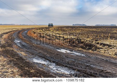 Agricultural landscape earth road on harvested maize field