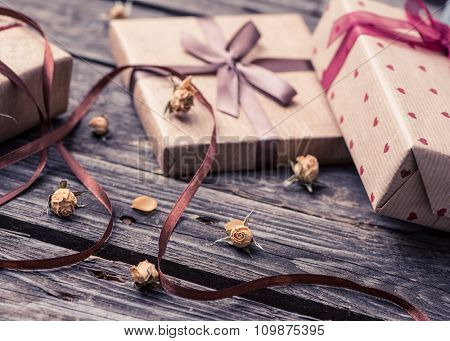 Holiday close-up background with dried rose flowers and vintage gift boxes