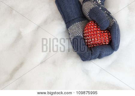 Woman Hands In Light Teal Knitted Mittens Are Holding Red Heart On Snow Background.