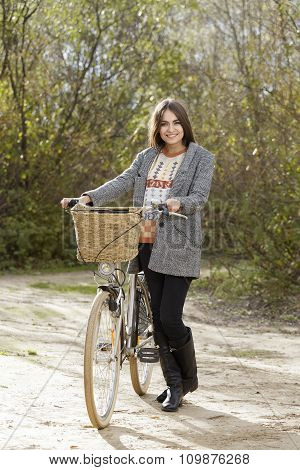 Young Female Walking With Bicycle In A Park