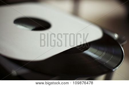 Close up view of old fashioned turntable playing a track from black vinyl toned