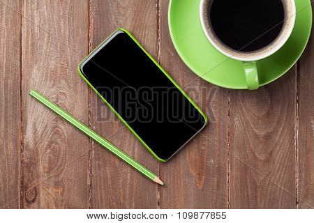 Office wooden desk with smartphone and coffee cup. Top view