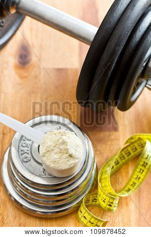 the whey protein in scoop and dumbbell