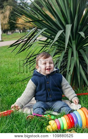 Happy one year boy in the park sitting on the green grass