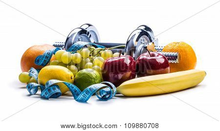 Chrome dumbbells surrounded with healthy fruits measuring tape on a  white background with shadows.