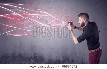 A stylish funny hipster person holding a vintage camera and taking photographs illustrated with glowing red, white lines concept