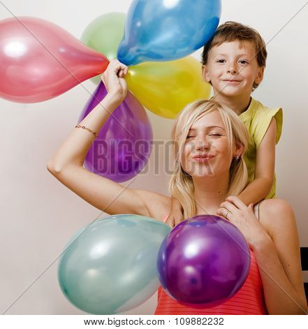 pretty real family with color balloons on white background, blond woman with little boy on birthday