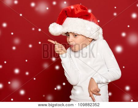 girl in santa hat dancing on red background with snow