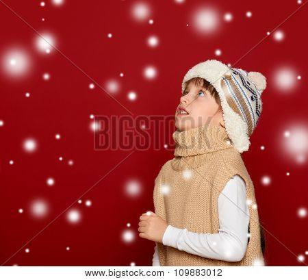 christmas concept - girl in hat and sweater on red background looking up