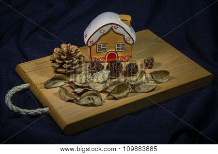 Ginger House On Wooden Board With Pine Cones.