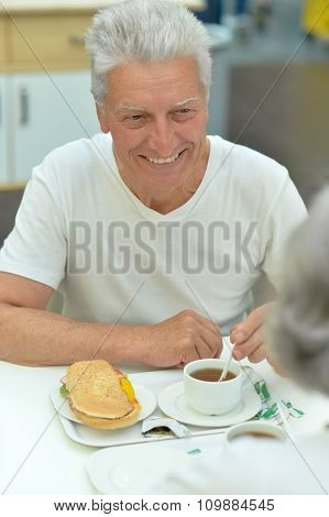 Senior couple with coffee and sandwich