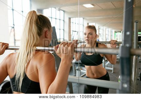 Woman Exercising With Barbell In Gym poster