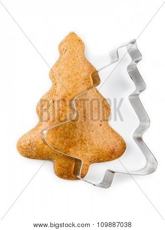 Christmas tree-like gingerbread cookie with metal cookie cutter on white background