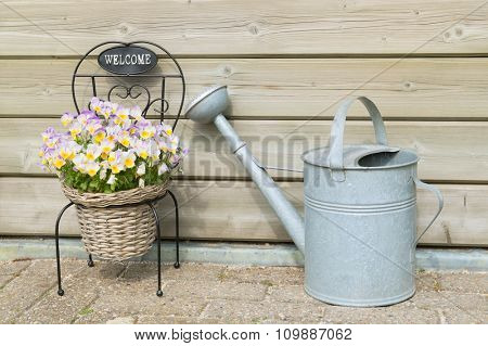 Welcome with viola flowers and watering can
