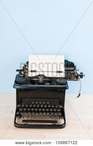Antique black typewriter on blue background