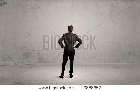 A confused sales person having a dilemma, standing with his back in empty grey urban environment concept