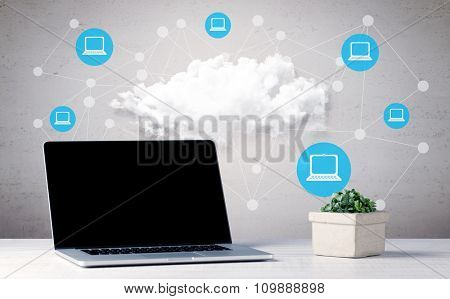 An office desk with laptop, flower, coffee, mobile phone and illustration in the background of connected computers around big white cloud