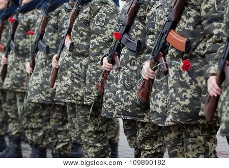Armed Soldiers in Camouflage Uniforms with Red Carnations and Automatic Weapons.