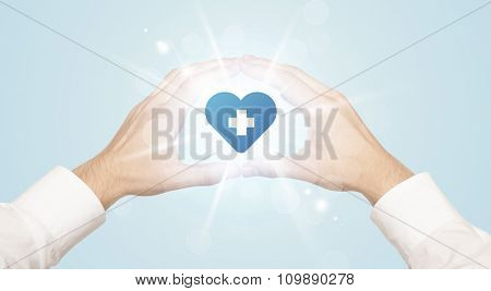 Hands creating a form with shining heart blue cross in the center