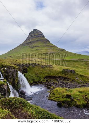 Iceland - the country of mountains, the rivers and falls. Cascade deep falls on the grassy mountains