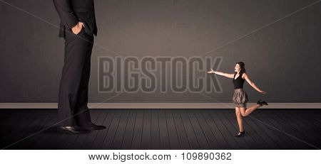 Little business woman in front of a giant boss legs concept on background