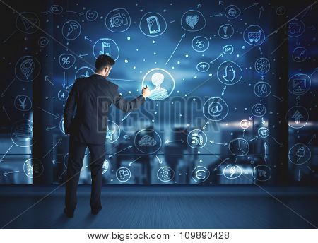 Businessman drawing social media connection scheme on glass window with night cityscape background