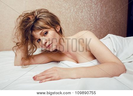 pretty blond woman laying in bed on white shits, sexy look