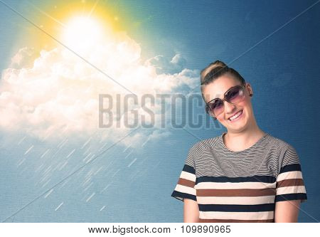 Young person looking with sunglasses at clouds and sun concept on blue background