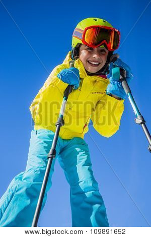 Skier girl enjoying winter vacation on a clear sunny day