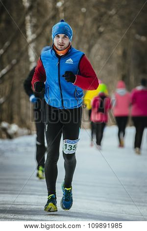 young male runner dressed for winter runs