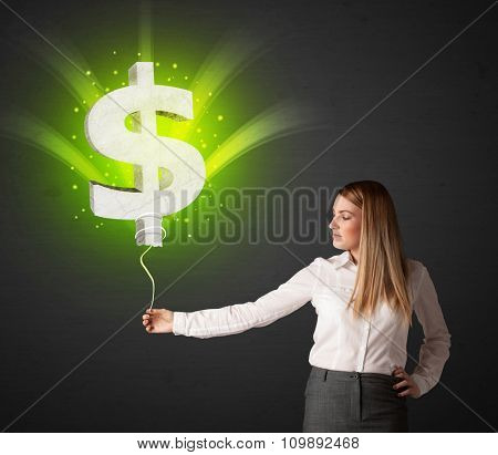 Businesswoman holding a shining, green dollar sign balloon