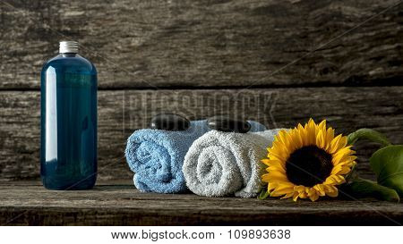 Still Life With Blue And White Rolled Towels With A Black Zen Stone On Top, Beautiful Blooming Sunfl