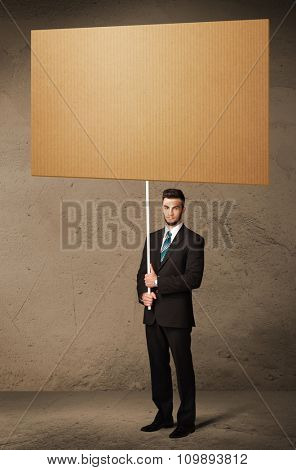 Young businessman holding a blank brown cardboard