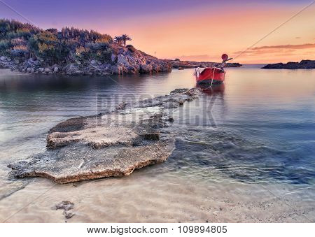 Amazing Coastal Landscape At Sunset. Rock Beach And Single Little Boat.