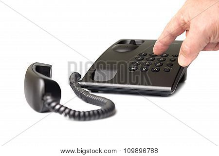Black push-button telephone and the hand that dials the number.