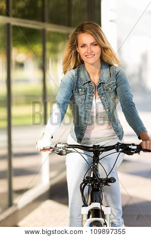 young happy smiling blonde beautiful woman wearing in white jeans riding bikes in park in bright sunlight on summer day
