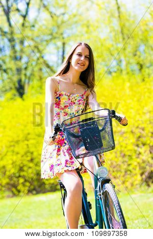 A girl wearing color dress with bike in summer park