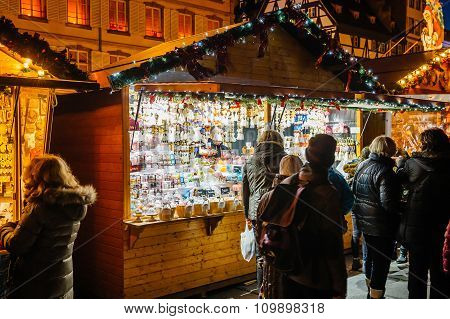 Christmas Market With People Admiring Gifts At Kiosk