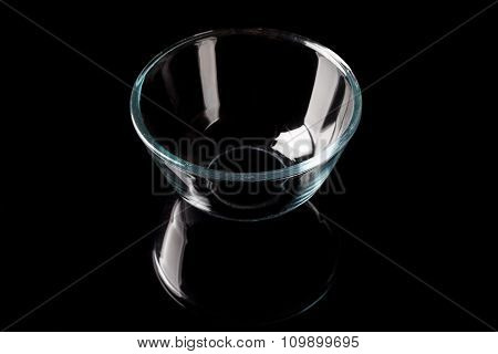 Glass bowl on black from high angle with reflection