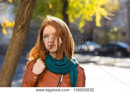 Portrait of sensual beautiful young redhead female in leather jacket and scarf in the street