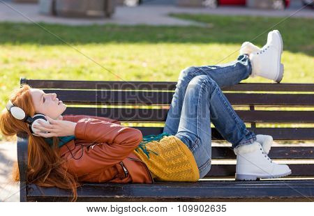Full length portrait of carefree young redhead lady in leather jacket, jeans and white boots lying on the bench in the park and listening to music
