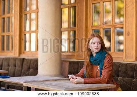 Pretty thoughtful redhead young woman holding her mobile phone and sitting at the table in outdoor cafe in autumn
